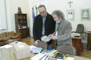 Roni Quevedo (dir) recebe da ONG Ação Pelo Semelhante doação de publicações homeopáticas